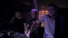 Three young djs ,illuminated from the disco lights, while they are mixing Stock Footage