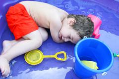 Toddler lying down in a pool - stock photo