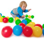 Comical child playing with colored plastic balls Stock Photos