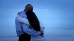 A closely slung love couple under a full moon 2 - stock footage