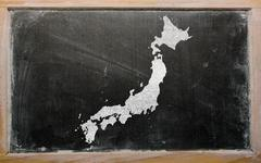 outline map of japan on blackboard - stock photo
