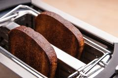 two hot bread toast in toaster - stock photo