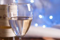 Glass and bottle white wine on blink light Stock Photos