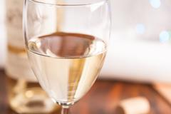 glass and bottle white wine on blink light - stock photo