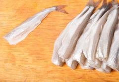 many uncooked trunk small fish on wood - stock photo