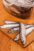 salted anchovies in box on wooden - stock photo