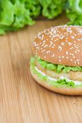 hamburger with chicken and withe sauce on wooden board - stock photo