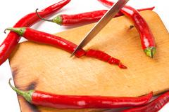hot capsicum chili pepper and knife on board - stock photo