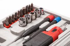 Open toolbox with screwdriver, heads and bit Stock Photos