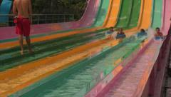 Lifeguard Watches Young People Racing Down Water Slides Stock Footage
