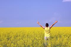happy teenager standing in an oilseed rape field - stock photo