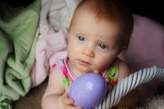 Infant with plastic Easter egg Stock Photos