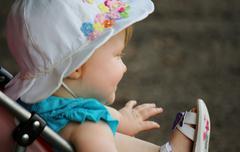Infant girl in stroller profile - stock photo