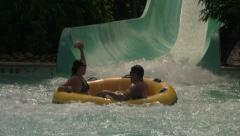 Family Sliding Down Water Park Slide in a Big Tube Stock Footage