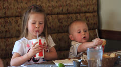 Children eating and drinking soda pop at restaurant Stock Footage