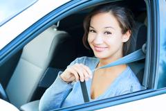 smiling young woman in car fastens seat belt - stock photo