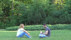 Young couple playing cards in the park Stock Footage
