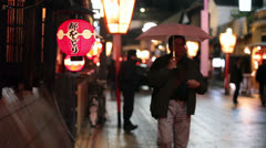 Lanterns on house and walking people at night, Gion, Kyoto, Japan Stock Footage