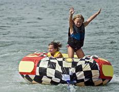 cute girls on tube behind boat - stock photo