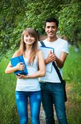 Two students studying in park with book outdoors Stock Photos
