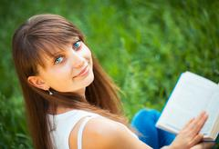beautiful girl with book in the park close up - stock photo
