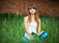 Stock Photo of beautiful girl with book in the park