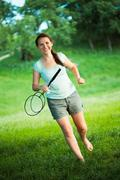 Smiling girl with a racket for a badminton in the park Stock Photos