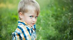 A cute little baby boy sit in the grass Stock Photos