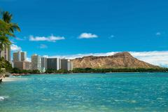 Stock Photo of waikiki beach with azure water in hawaii with diamond head in background.