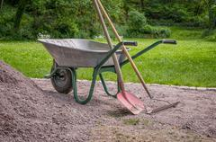 Wheelbarrow with shovel and rake Stock Photos