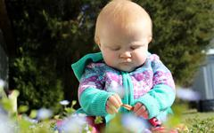 Infant girl in flowers Stock Photos