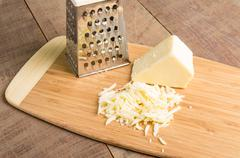 parmesan cheese grated on a cutting board - stock photo
