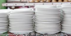 Stacks of white plates in warehouse Stock Photos
