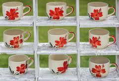 many coffee mugss dispaly on the white wooden shelves ingarden. - stock photo