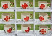 Many coffee mugss dispaly on the white wooden shelves ingarden. Stock Photos