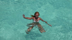 The happy woman in the sea waves to us greeting a hand - stock footage