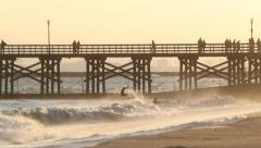 Skim Boarders Jump Waves by Pier at Sunset Stock Footage