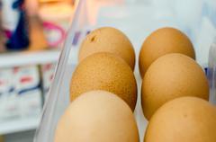 six eggs stored in the refrigerator door - stock photo