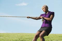 Stock Photo of competitive businesswoman playing tug of war with rope