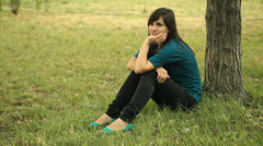 Superb Beautiful Young Adult Woman Sits by Tree Stock Footage