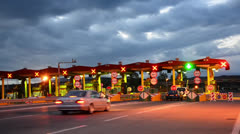 Highway car paytoll at sunrise, night lights and autos passing through toll b Stock Footage