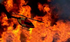 Helicopter flying by a bushfire Stock Photos