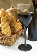 Stock Photo of still life assortment of bread with a glass of red wine and bottle.