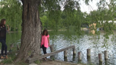 Two cheerful  girls in park, near water . Stock Footage
