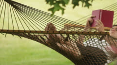 man reading a book in a hammock - stock footage