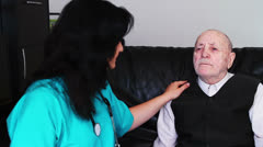 Senior man talking with nurse at home Stock Footage