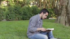 Boy reads a book in the park but is interrupted by prank of a friend Stock Footage