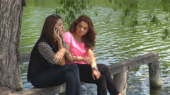 Two cheerful  girls in park, near water .Talking on the phone Stock Footage