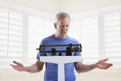 Caucasian man weighing himself Stock Photos