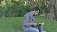 Stock Video Footage of boy reads a book in the park but is interrupted by prank of a friend
